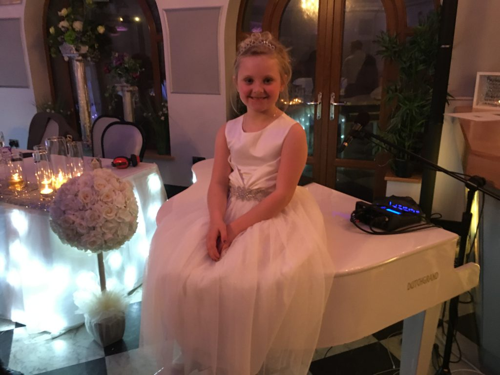 Mr & Mrs Armitage's niece on the white baby grand piano